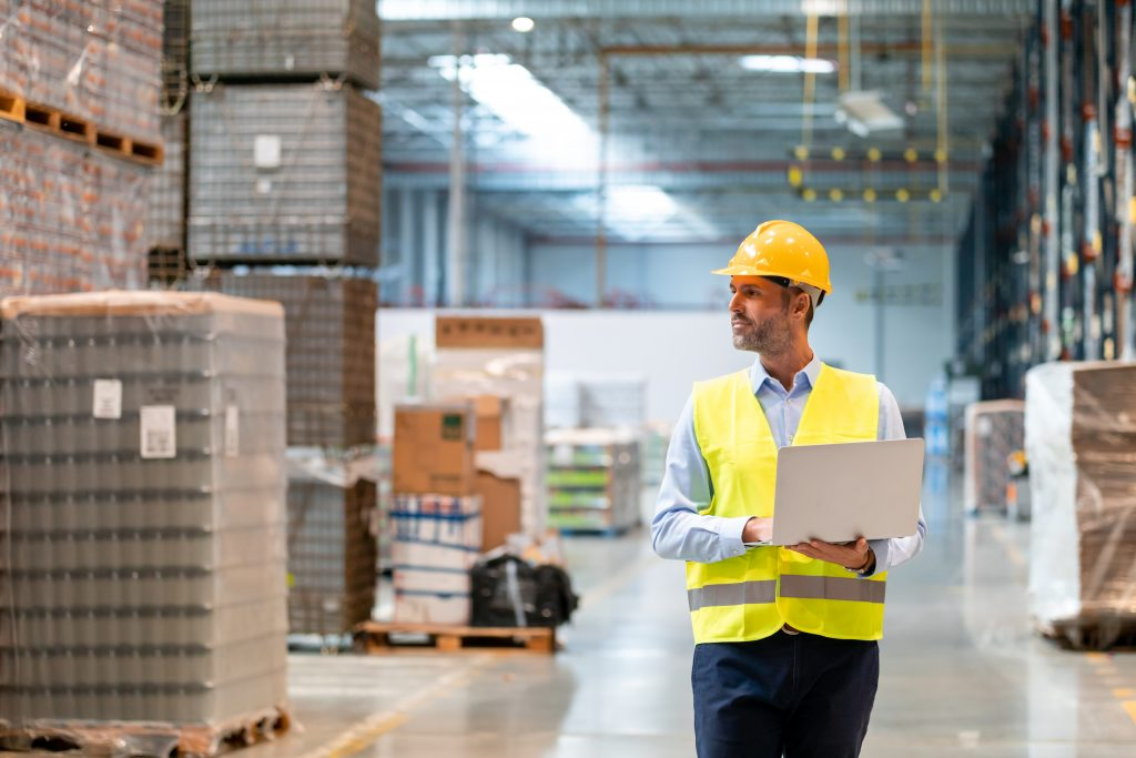 Warehouse worker using laptop and entering data to database